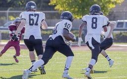 Corrida dos jogadores de futebol da High School Fotografia de Stock