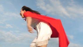 Corrida e riso engra?ados da menina do super-her?i no casaco vermelho, casaco que vibra no vento A jovem mulher alegre joga no su filme