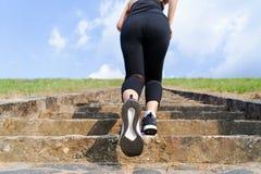 Corrida nova da mulher do esporte exterior em cima no céu azul imagem de stock