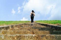 Corrida nova da mulher do esporte exterior em cima no céu azul imagem de stock royalty free