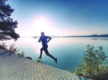 Corrida regular no lago Sprinting do corredor do homem exterior na natureza cénico foto de stock