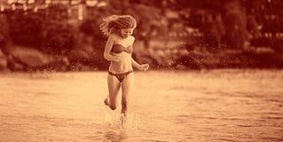 Corridas bonitas da menina ao longo da praia Fotografia de Stock Royalty Free
