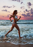 Corridas da menina ao longo da praia Imagens de Stock
