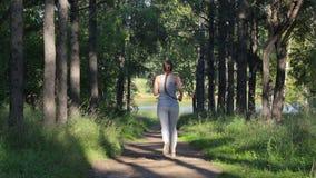 Corridas da menina ao longo de uma aleia obscuro do verde floresta Mulher nova que movimenta-se no parque filme