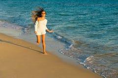 Corridas da menina ao longo do litoral Imagem de Stock