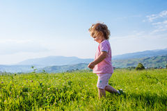 Corridas da menina através de um prado bonito imagem de stock