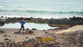 Corridas da mulher ao longo da costa rochoso do oceano Estilo de vida ativo saud?vel Filmado nas velocidades diferentes - lentas  video estoque