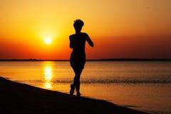 Corridas da rapariga ao longo da costa de mar Fotografia de Stock