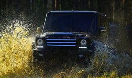 Corridas de carros no extremo da floresta do outono, no desafio e no conceito do veículo 4x4 SUV ou carro offroad no trajeto cobe Foto de Stock