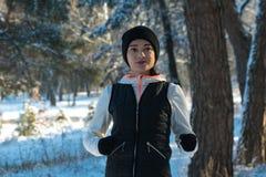 Corridas de corrida de corrida da menina da neve do inverno através das madeiras no inverno do esporte de inverno Estilo de vida  imagem de stock