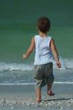 Corridas del muchacho para practicar surf la línea Imágenes de archivo libres de regalías
