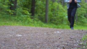 Corridas do homem ao longo do trajeto na floresta que a câmera dispara de baixo de filme