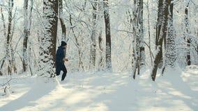 Corridas do homem no inverno em um trajeto de floresta filme