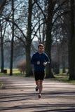 Corridas do homem novo através do parque Fotos de Stock Royalty Free