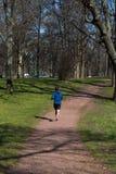 Corridas do homem novo através do parque Fotografia de Stock Royalty Free