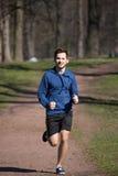 Corridas do homem novo através do parque Imagens de Stock