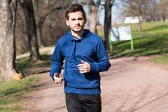 Corridas do homem novo através do parque Imagens de Stock Royalty Free