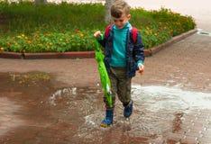 Corridas do menino através da poça Fotos de Stock Royalty Free