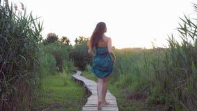 Corridas fêmeas felizes bonitas descalças na ponte de madeira fora e nas voltas para olhar a câmera video estoque