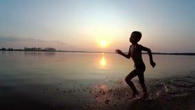Corridas felizes da criança ao longo da praia no por do sol Movimento lento