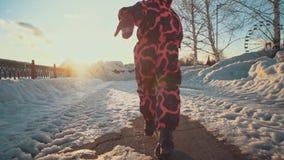 Corridas felizes da menina nos trajetos da neve no parque vídeos de arquivo