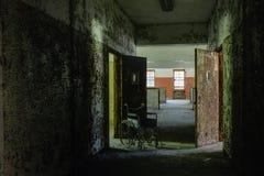 Corridoio con la sedia a rotelle d'annata & le porte aperte - ospedale abbandonato immagine stock