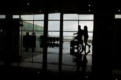 Corridoio del terminale di aeroporto con alcuni viaggiatori fotografia stock libera da diritti
