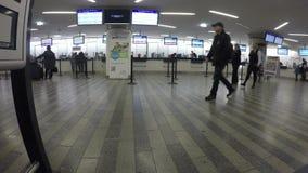 Corridoio dell'aeroporto o della stazione ferroviaria, biglietti d'acquisto della gente alle finestre dell'ufficio di prenotazion video d archivio