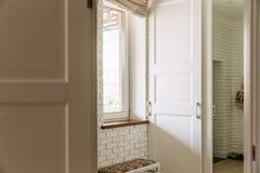 Corridoio illuminato buono con la finestra sulla parete sinistra ed il corridoio sui precedenti immagini stock libere da diritti