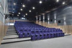 Corridoio interno del cinema con abbondanza di disposizione dei posti a sedere e di un proiettore Fotografie Stock Libere da Diritti