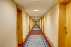 Un corridoio lungo e stretto con la prospettiva chiusa delle porte.