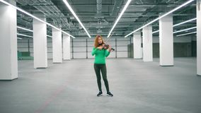 Corridoio spazioso con un violinista femminile che gioca lo strumento stock footage