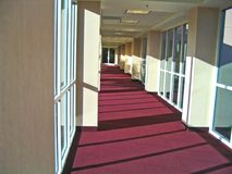 Corridor. A hallway between buildings, with numerous long windows and mauve industrial carpeting Royalty Free Stock Photos