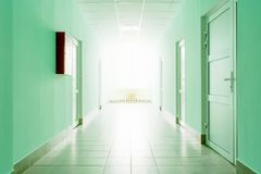The corridor with bright light from the window, a hall with green walls and white doors. Corridor with bright light from the window, a hall with green walls and Royalty Free Stock Photo