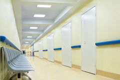 Corridor with chairs in hospital. Long empty yellow corridor with chairs in hospital