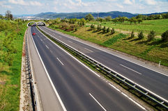 Corridor highway with the transition for animals, in the distance three red car Royalty Free Stock Photos