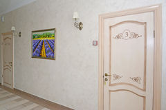 Corridor of hotel with white doors in numbers and a picture on a Royalty Free Stock Photography