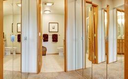 Corridor with mirror door closets and bathroom view. Through the open door stock photos