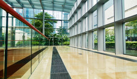 Inside modern glass office building. Corridor inside modern glass office building. Interior of modern business commercial building with glass and steel frame Royalty Free Stock Photos