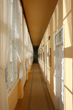 Narrow bright corridor. Narrow empty corridor ending in darkness Stock Photography