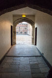 Corridor out to court yard at hampton court. A stone flagged floor leading through an arch out to a cobbled square Royalty Free Stock Image