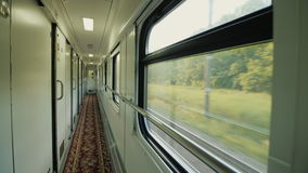 Corridor of the passenger railway car. A number of windows and doors, the train is moving fast. In the train car, a long corridor with a door in the compartment stock footage