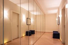 Corridor with wardrobes and mirrors. Modern lights on the floor. Nobody inside stock image