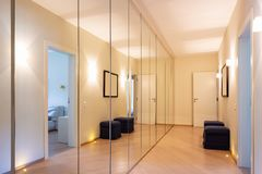 Corridor with wardrobes and mirrors. Modern lights on the floor. Nobody inside royalty free stock images