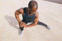Corridore in abiti sportivi neri che allungano le gambe prima del fare allenamento di mattina Fotografia Stock