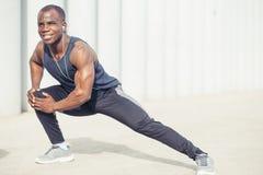 Corridore in abiti sportivi neri che allungano le gambe prima del fare allenamento di mattina Immagini Stock