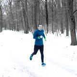 Corridore adulto dell'uomo che corre nella foresta nell'inverno fotografie stock libere da diritti