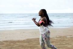 Corridore africano femminile che pareggia durante l'allenamento all'aperto sulla spiaggia Immagine Stock
