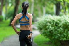 Corridore asiatico della donna di forma fisica che allunga le gambe prima dell'allenamento all'aperto di funzionamento nel parco fotografie stock libere da diritti