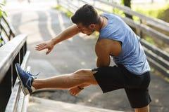 Corridore atletico che fa allungando esercizio, preparante per l'allenamento di mattina nel parco Fotografia Stock Libera da Diritti